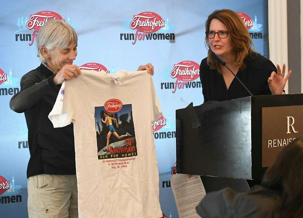 Masters athlete Joan Benoit-Samuelson, left, presents her shirt from the 20th Anniversary Freihofer's Run For Women race in 1998 to Christine Ammon, director of human relations, Charles Freihofer's Bakery Company, as the Freihofer's Run For Women holds its press conference at the Renaissance Albany Hotel on Friday, June 1, 2018 in Albany, N.Y. This year will be the 40th anniversary of the race. (Lori Van Buren/Times Union)