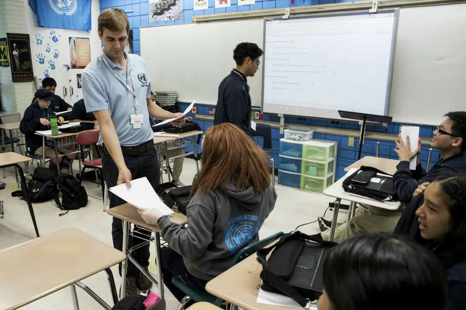 John Sigren passes out papers in his social studies class at HISD's Sharpstown International School. HISD's Sharpstown International School is the No. 8 ranked high school in the region in the report card category, and the only school in the top 10 with more than 1,000 students. Photo: Brett Coomer, Staff / Houston Chronicle / © 2018 Houston Chronicle
