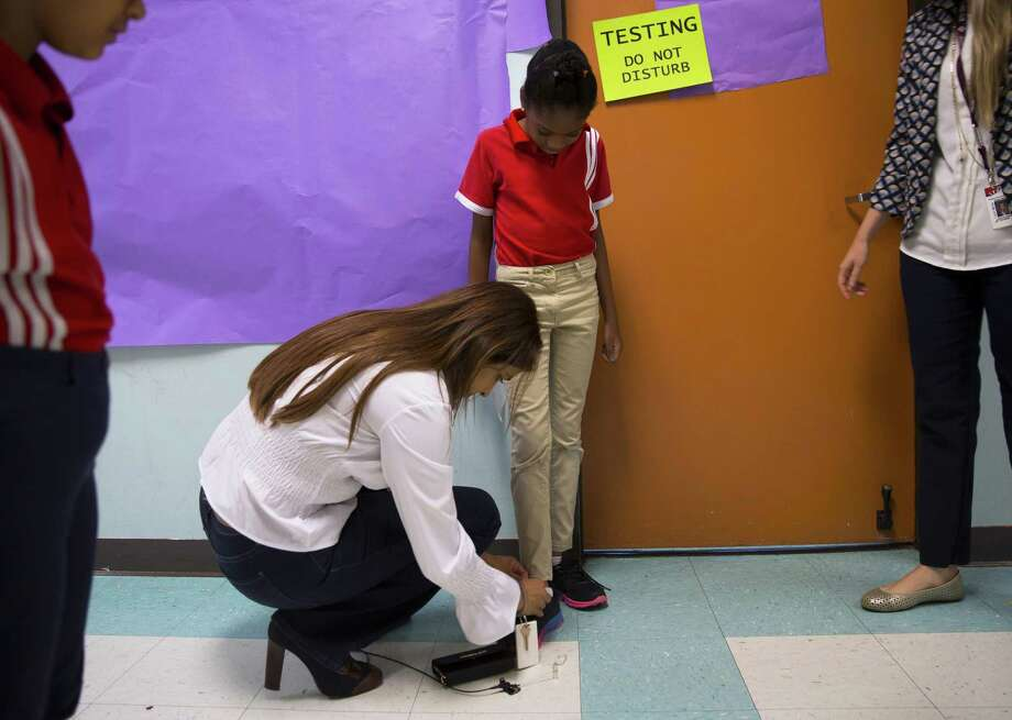 Principal Afreen Merchant stops to tie first grader Naiya Stewart's shoe during a tour of the Harmony Science Academy of Sugar Land. Photo: Annie Mulligan, Freelance / Annie Mulligan / @ 2018 Annie Mulligan