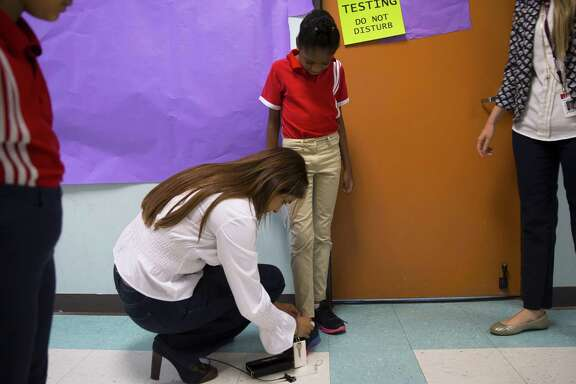 Principal Afreen Merchant stops to tie first grader Naiya Stewart's shoe during a tour of the Harmony Science Academy of Sugar Land.