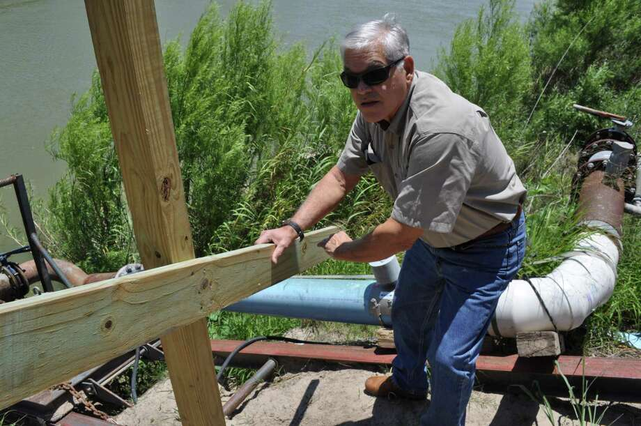 Frank Schuster checks on an irrigation pump on a part of his farm that will be south of the border wall. He doesn't believe the border wall is the right thing to do, but is not fighting its construction, which will run through his property, co-owned with his sister, Becky Jones. Photo: Josh Brodesky /