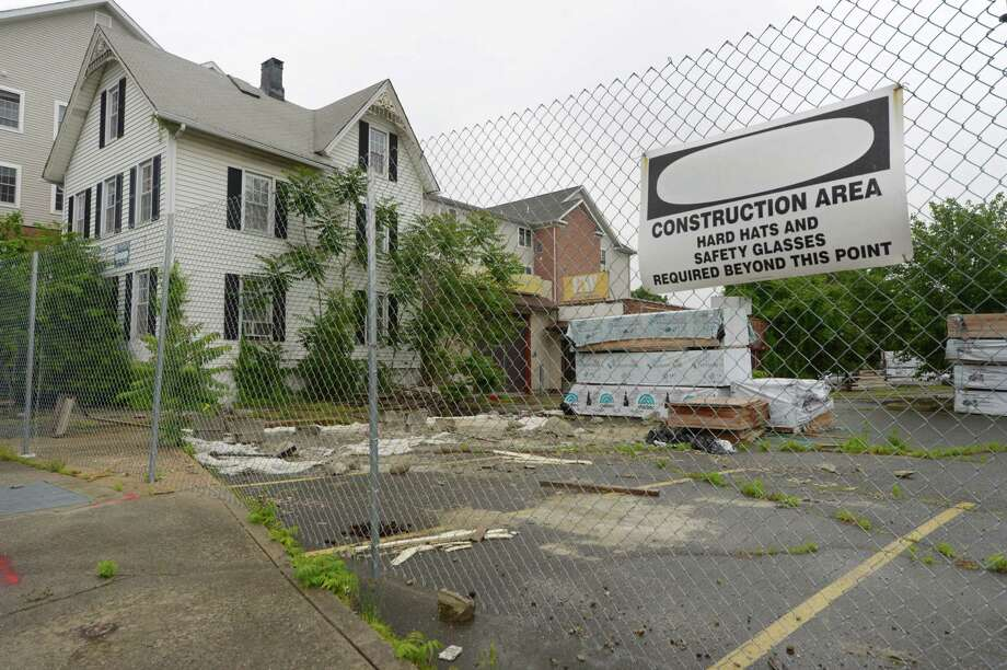 The parking lot at 23 Isaac Street and the house at 21 Isaac Street on Thursday, May 31, 2018, were cited for blight last month by the city in Norwalk, Conn. The properties were part of the abandoned Wall Street Place development and are being sought for purchase by real estate owner Jason Milligan. Photo: Erik Trautmann / Hearst Connecticut Media / Norwalk Hour