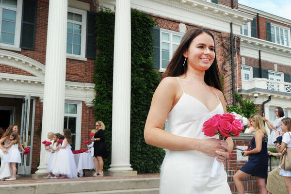 Annabell Knollmeyer of Bedford, N.Y., smiles as she holds a bouquet of red roses during her Sacred Heart Greenwich commencement at the school in Greenwich, Conn., Friday, June 1, 2018.