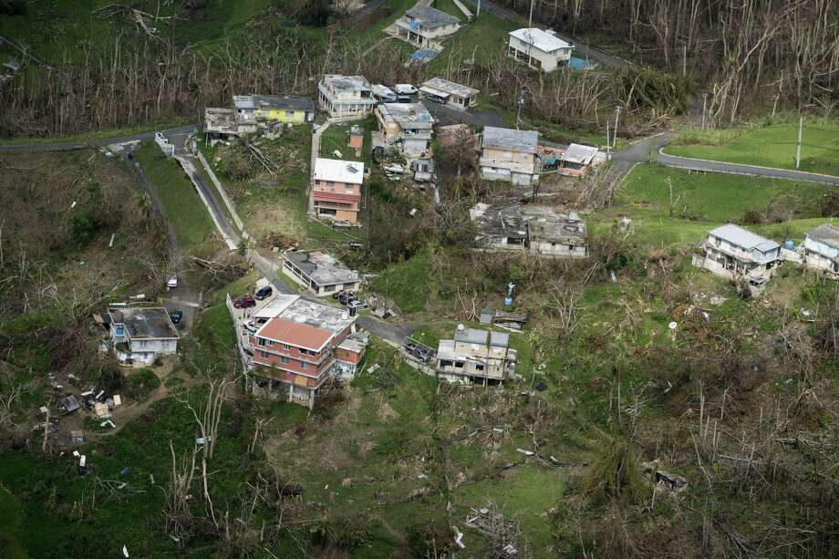 Homes damaged during Hurricane Maria, seen during Donald Trumps visit to the San Juan, Puerto Rico, Oct. 3. A new study by a group of independent researchers at Harvard University concludes that the hurricane caused roughly 4,600 deaths, many of them due to delayed medical care, far surpassing the federal count. Photo: DOUG MILLS /NYT / NYTNS