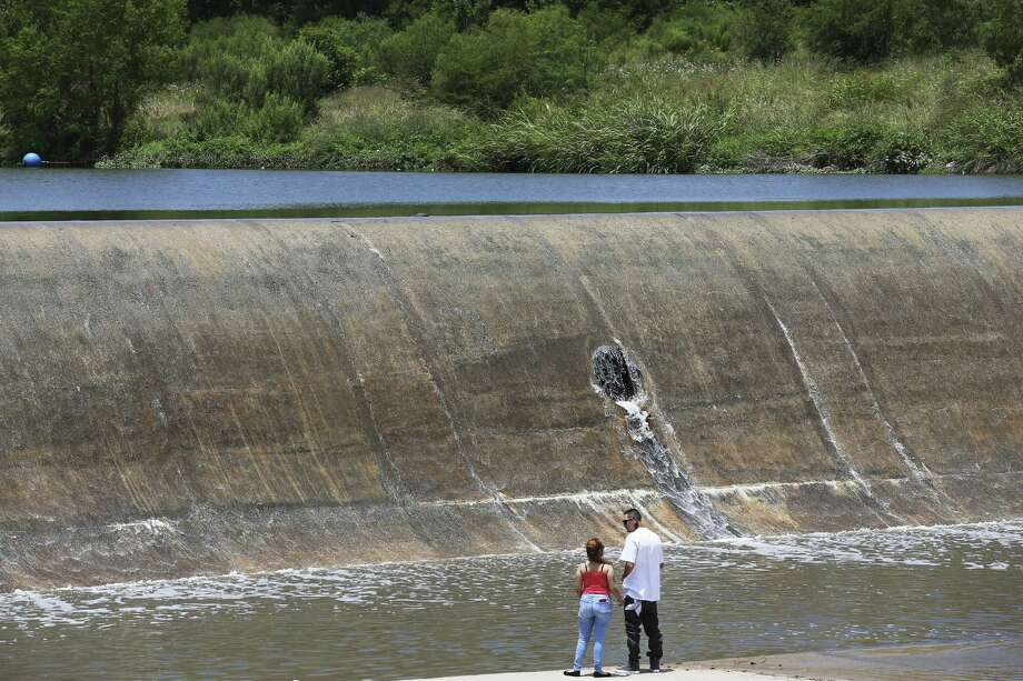 Irving Morales, 27, and Jennifer Covarruvias, 29, watch as water flows over Espada Dam in south San Antonio May 21. Among the possible casualties of unchecked climate change? The Edwards Aquifer. Photo: JERRY LARA /San Antonio Express-News / San Antonio Express-News
