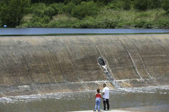 Irving Morales, 27, and Jennifer Covarruvias, 29, watch as water flows over Espada Dam in south San Antonio May 21. Among the possible casualties of unchecked climate change? The Edwards Aquifer.