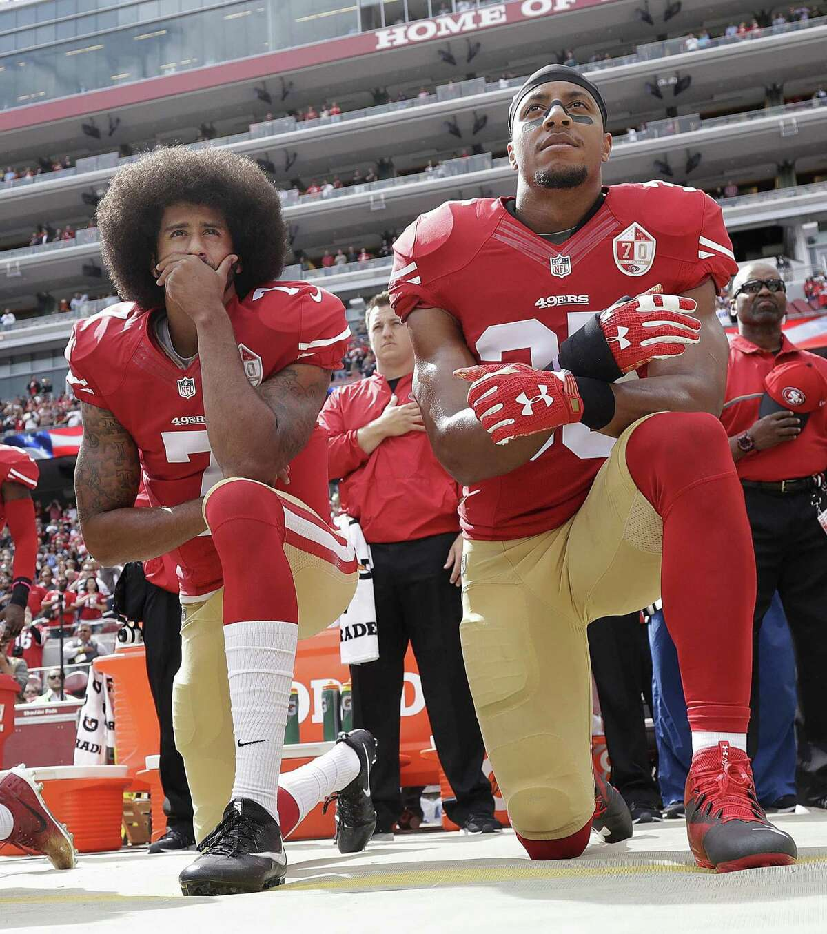 San Francisco 49ers quarterback Colin Kaepernick, left, and safety Eric Reid kneel during the national anthem before an NFL football game in 2016.
