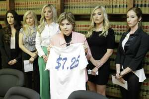Attorney Gloria Allred stands among former Houston Texans cheerleaders Ashley Rodriguez, left, Morgan Wiederhold, Kelly Neuner, Hannah Turnbow, and Ainsley Parish, right, holding up a shirt printed with $7.25, the amount she says the former cheerleaders where paid per hour, as she speaks during a press conference announcing a lawsuit on behalf of the five the former cheerleaders shown at the law offices of Kimberley Spurlock, 17280 West Lake Houston Parkway, in Humble,  Friday, June 1, 2018. ( Melissa Phillip / Houston Chronicle )