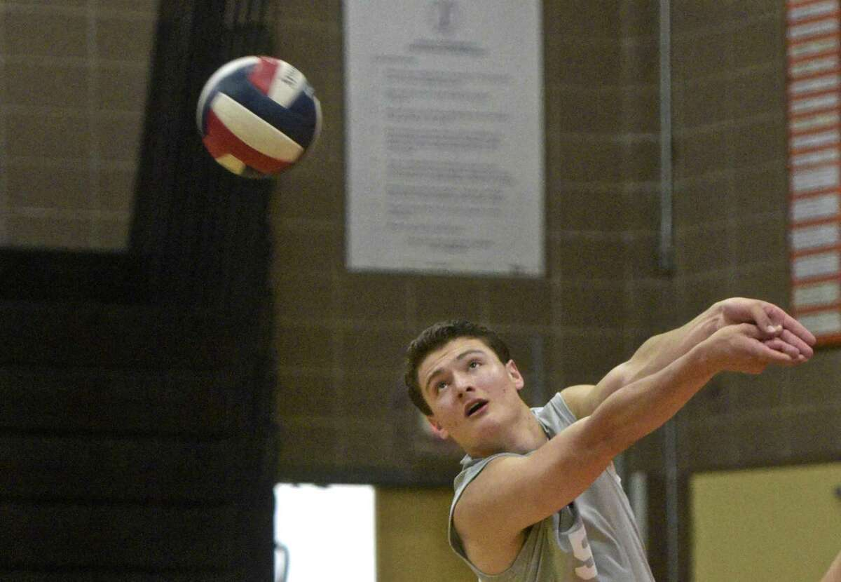 Darien's Anthony Barsanti returns a serve in the Class L volleyball game between Darien and Ridgefield high schools on Friday afternoon.