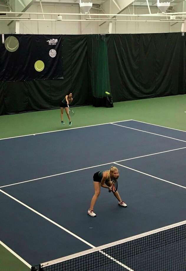 Dow's Amelie Kraef, foreground, and Reema Patel, serving in background, have won all 19 of their No. 4 doubles matches this season without losing a single set. (Photo provided)