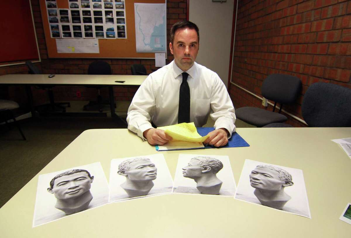 Milford Police Department's Detective Mitchell Warwick, who is responsible for two cold cases, poses at police headquarters in Milford, Conn. on Wednesday May 9, 2018. The photos in front of Det. Warwick depict the reconstructed face made from the skull. On Aug. 21, 1992, a couple walking on Oronoque Road in Milford, Conn., saw what they thought was a carpet on the side of the road across from the train tracks. When they pulled back what was a blanket, they saw the skeletal remains of an unidentified man.