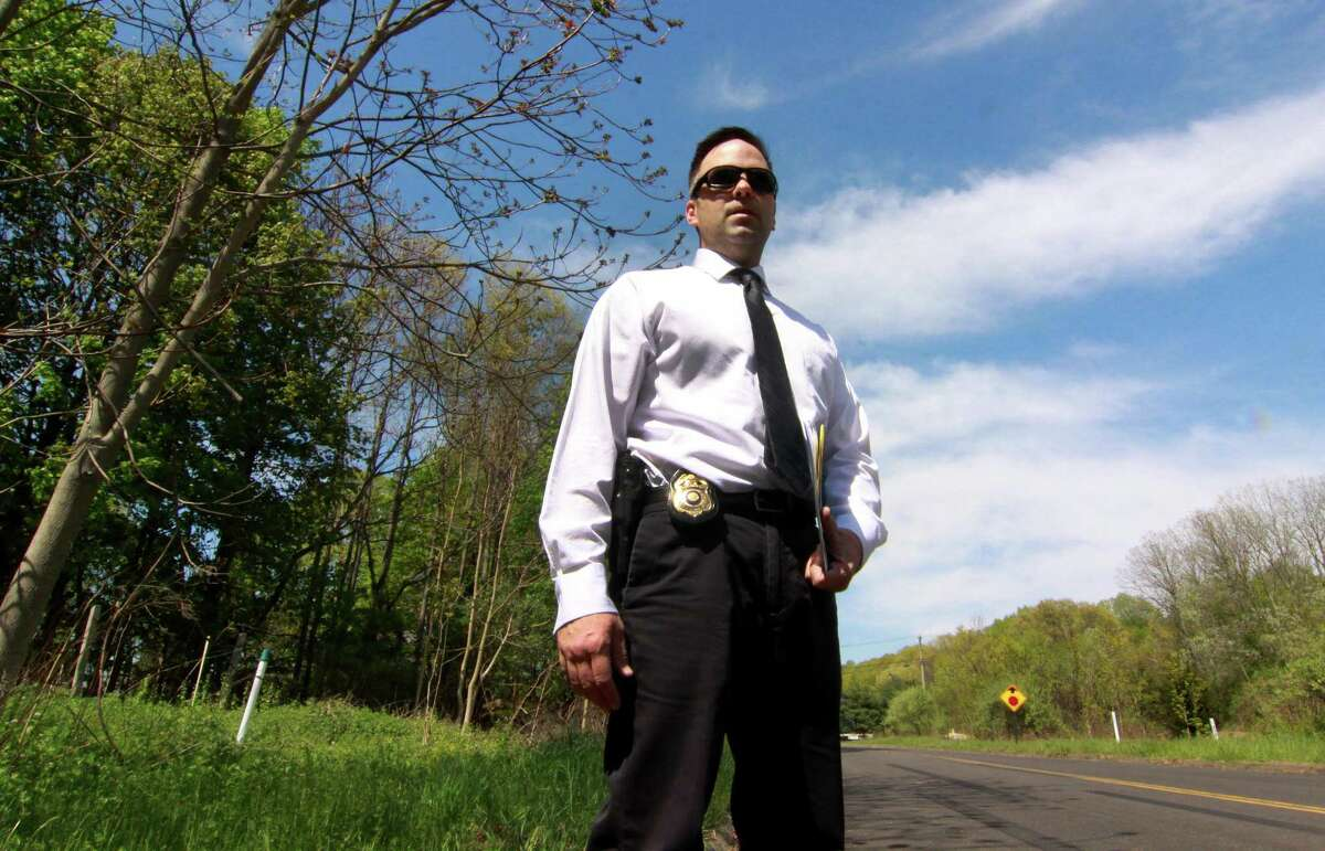 Milford Police Department's Detective Mitchell Warwick, who is responsible for two cold cases, stands near the scene of one of them on Oronoque Road in Milford, Conn. on Wednesday May 9, 2018. On Aug. 21, 1992, a couple walking on Oronoque Road in Milford, Conn., saw what they thought was a carpet on the side of the road across from the train tracks. When they pulled back what was a blanket, they saw the skeletal remains of an unidentified man.