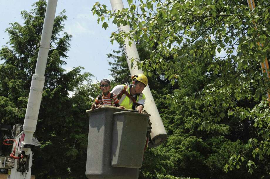 A youngster gets a ride in a bucket truck during a previous Touch a Truck event in Greenwich. The Junior League of Greenwich is hosting the 18th annual fundraising event on June 10 at Greenwich Town Hall. Photo: File / Helen Neafsey / Helen Neafsey / Greenwich Time