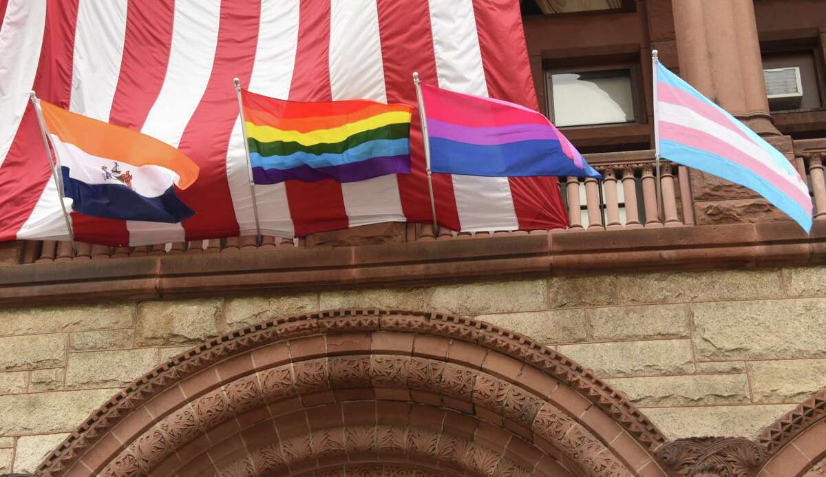 Left to right starting second from left, the Rainbow Flag, the Transgender Flag and the Bi-Sexual Flag are seen during the annual Pride Flag raising ceremony to celebrate Pride Month at City Hall on Friday, June 1, 2018 in Albany, N.Y. The three flags are symbols of the LGBTQ movement. (Lori Van Buren/Times Union)