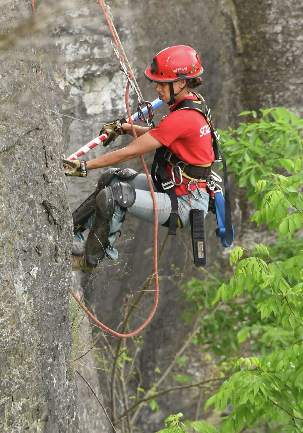 A member of New York State Parks Recreation & Historic Preservation scaling team pokes loose rocks as she rappels down the rocky cliff above Indian Ladder Trail at John Boyd Thacher State Park on Thursday, May 31, 2018 in Voorheesville, N.Y. The scaling team, out of Ithaca, was poking loose rocks to make them fall to prevent future injuries to hikers. (Lori Van Buren/Times Union)
