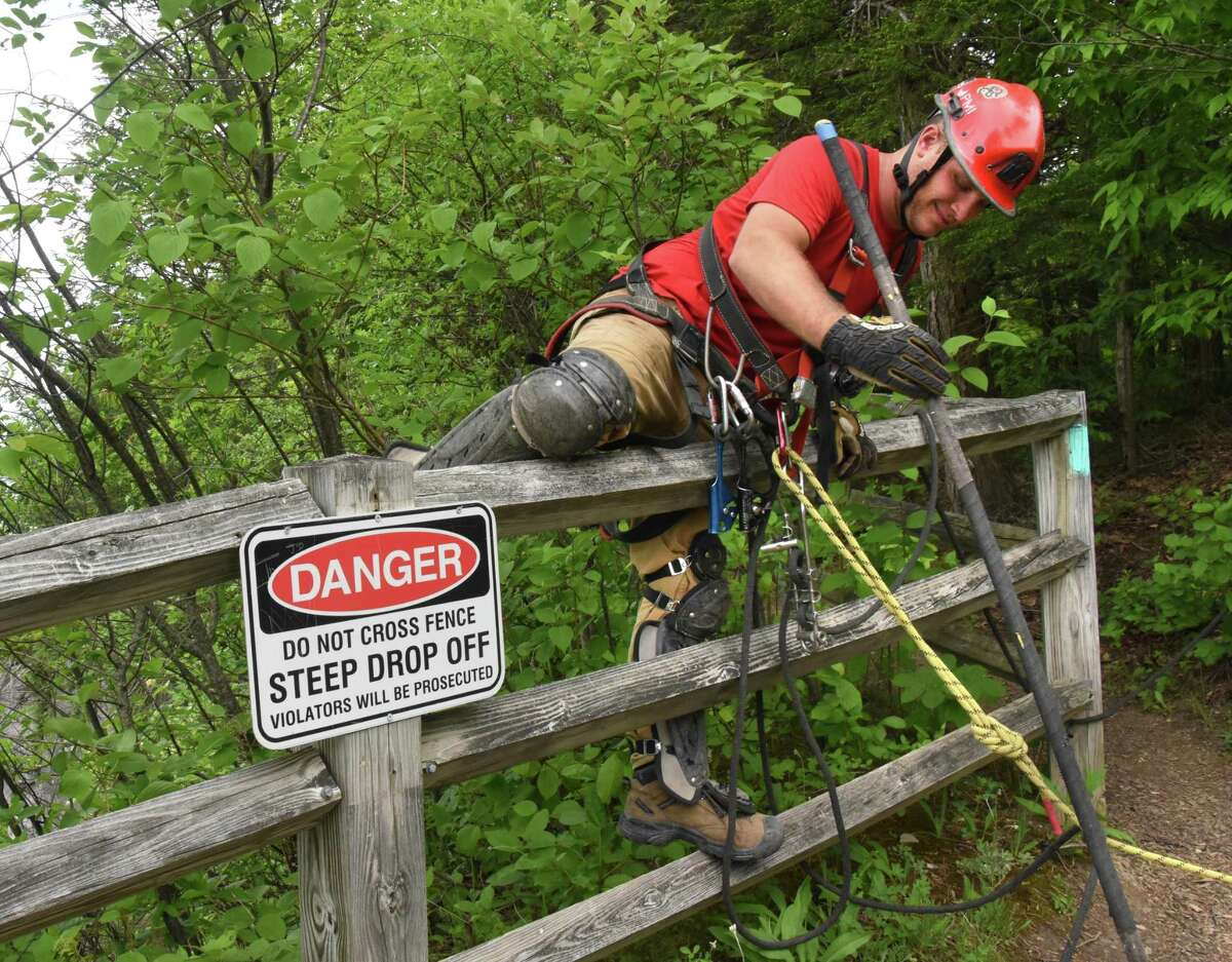 A member of New York State Parks Recreation & Historic Preservation scaling team climbs over a fence before rappelling down the rocky cliff above Indian Ladder Trail at John Boyd Thacher State Park on Thursday, May 31, 2018 in Voorheesville, N.Y. The scaling team, out of Ithaca, was poking loose rocks to make them fall to prevent future injuries to hikers. (Lori Van Buren/Times Union)