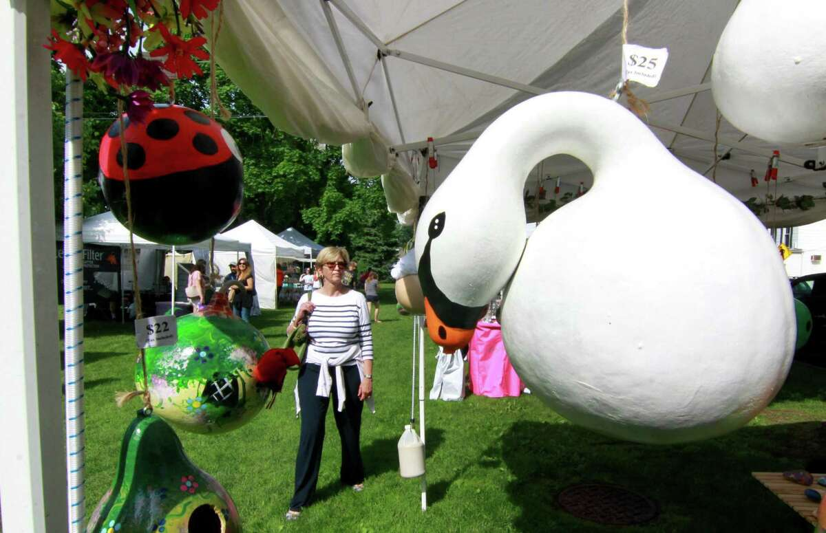 Sonia Gabiola, of Sagaponack, NY, strolls past art and craft tents with hand crafted items for sale during Mary Taylor Memorial United Methodist Church annual two-day craft fair on the downtown Milford green in Milford, Conn., on Friday, June 1, 2018. The swan on display in the foreground is a bird house made from a gourd by local business Sweet Re-Tweet. The annual event, marks its 47th year this June, and draws an abundance of visitors from Milford and the surrounding shore towns and features more than 100 craft and other vendors. The fair continues on Saturday June 2nd from 10 a.m. to 5 p.m.