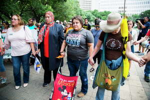 (Left to right) Jennifer Cantu, Dalia Kasseb and Eliz Markowitz join hands in prayer during a protest against the separation of families when they are arrested crossing the border. The rally and protest started at Houston City Hall and ended in front of the U.S. District Courthouse at 515 Rusk St., Friday, June 1, 2018, in Houston.