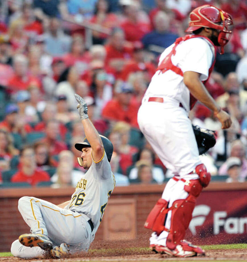 The Pirates' Adam Frazier (26) scores on a sacrifice fly by teammate Josh Bell as Cardinals catcher Francisco Pena waits for the ball in the third inning Friday night's game at Busch Stadium. Photo:       AP