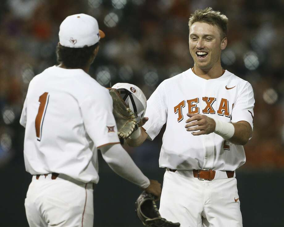 Kody Clemens, left stranded after getting an RBI, accepts his gear from David Hamilton as the Longhorns take the field as Texas  plays Texas Southern University at Disch-Falk Field in Austin in the first round of the NCAA Regional playoffs on June 1, 2018. Photo: Tom Reel/San Antonio Express-News