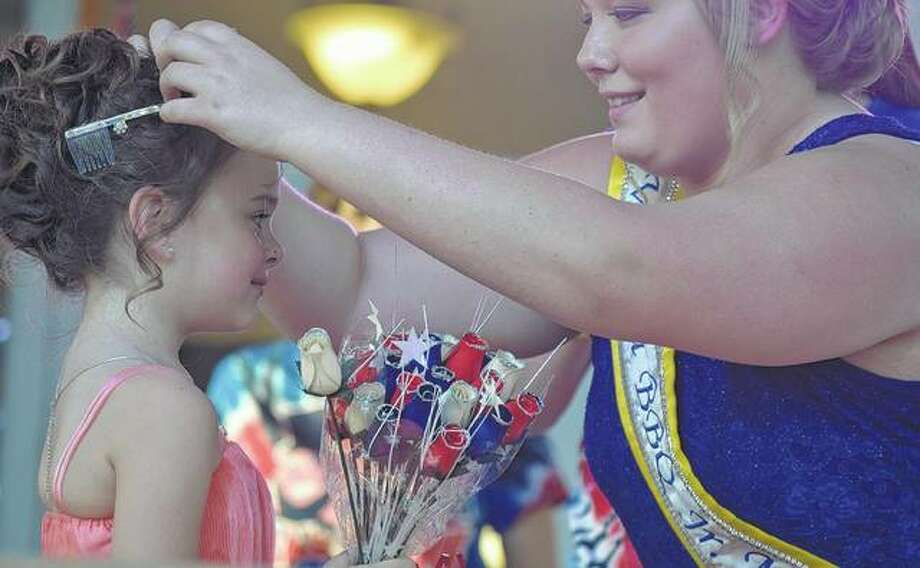 Little Miss Virginia BBQ Prestley Angelo receives her crown Friday from 2017 Junior Miss Virginia BBQ Emily Pratt during the 2018 Little and Junior Miss Virginia BBQ competition. Photo:       Samantha McDaniel-Ogletree | Journal-Courier