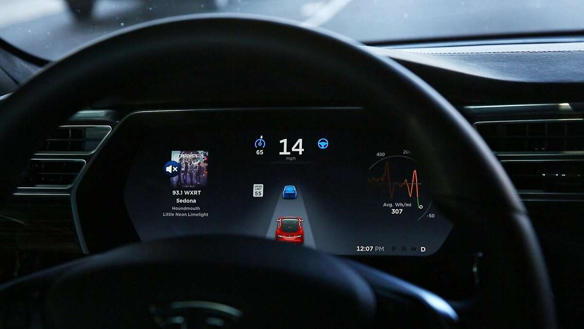 The dashboard of the software-updated Tesla Model S P90D shows the icons enabling Tesla's autopilot, featuring limited hands-free steering. Car-hacking is a threat that could become serious in the future, when driverless vehicles begin talking to one another. (Chris Walker/Chicago Tribune/TNS)
