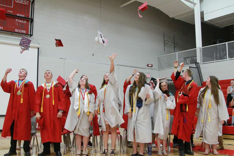 Owendale-Gagetown graduates toss their hats high, and proud, Thursday night following their graduation ceremony. Photo: Coulter Mitchell/For The Tribune