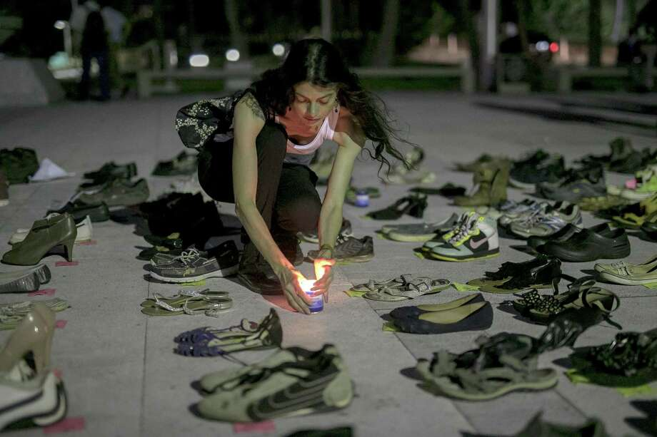 A demonstrator places a candle next to empty pairs of shoes displayed outside the Capital building during a protest against the government's reporting of the death toll from Hurricane Maria in San Juan, Puerto Rico, on Friday, June 1. Hurricane Maria probably killed about 5,000 people in Puerto Rico last year even though the official count remains at just 64, according to a Harvard University study released Tuesday. Photo: Xavier Garcia / Bloomberg / © 2018 Bloomberg Finance LP