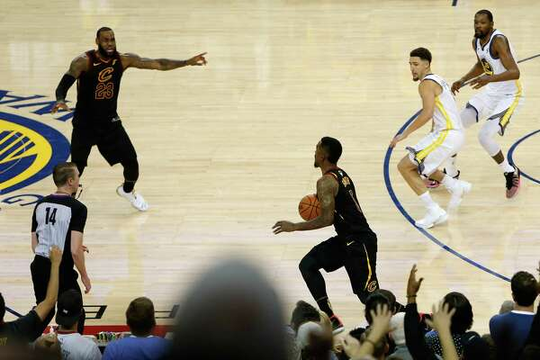The Cavaliers JR Smith, center, dribbles in the closing seconds of regulation as LeBron James attempts to direct the offense in Game 1 of the NBA Finals.