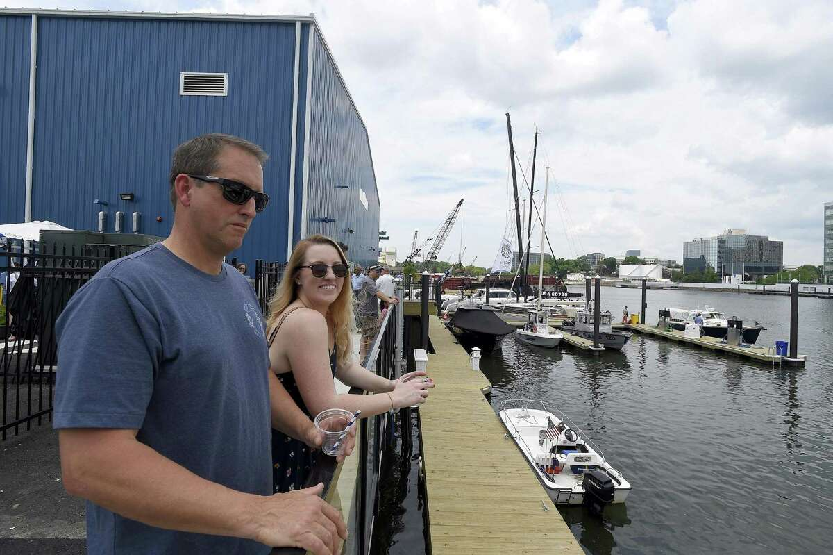 Dean Lindquist, of Newtown, and his daughter, Brittany Lindquist, of Stamford, take in the picturesque views of Stamford's west branch of the Rippowam River during the grand opening of Hinckley boatyard on Saturday.