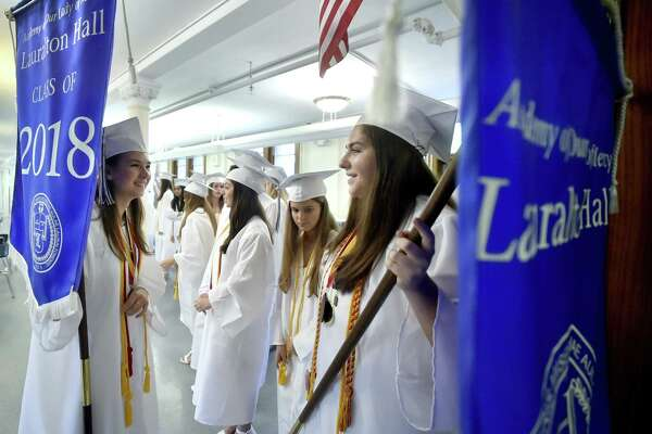 Milford, Connecticut - June 2, 2018: Lauralton Hall Salutatorian Lily Wald of Derby, left, and Valedictorian Caroline Favano of Norwalk right, hold on to Lauralton Hall banners as the wait to lead the Lauralton Hall Class of 2018 Graduation processional Saturday at Lauralton Hall in Milford.