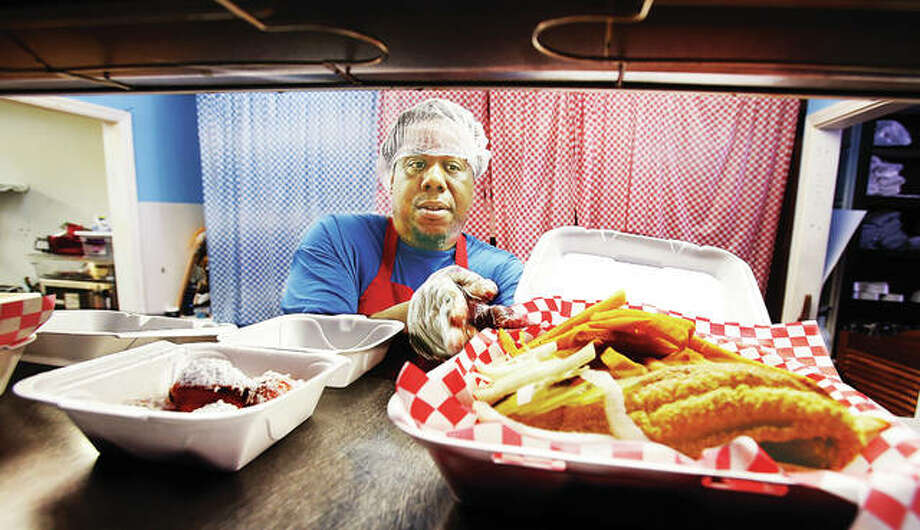 Brad Chavours dishes up some hot food at the restaurant his mother, Merry Lovett, started at 2512 College Ave. in Upper Alton, last year, during its third anniversary. Lovett's Snoots, Fish, Chicken & More now simply goes by Lovett's Soul Food. Photo:       John Badman The Telegraph