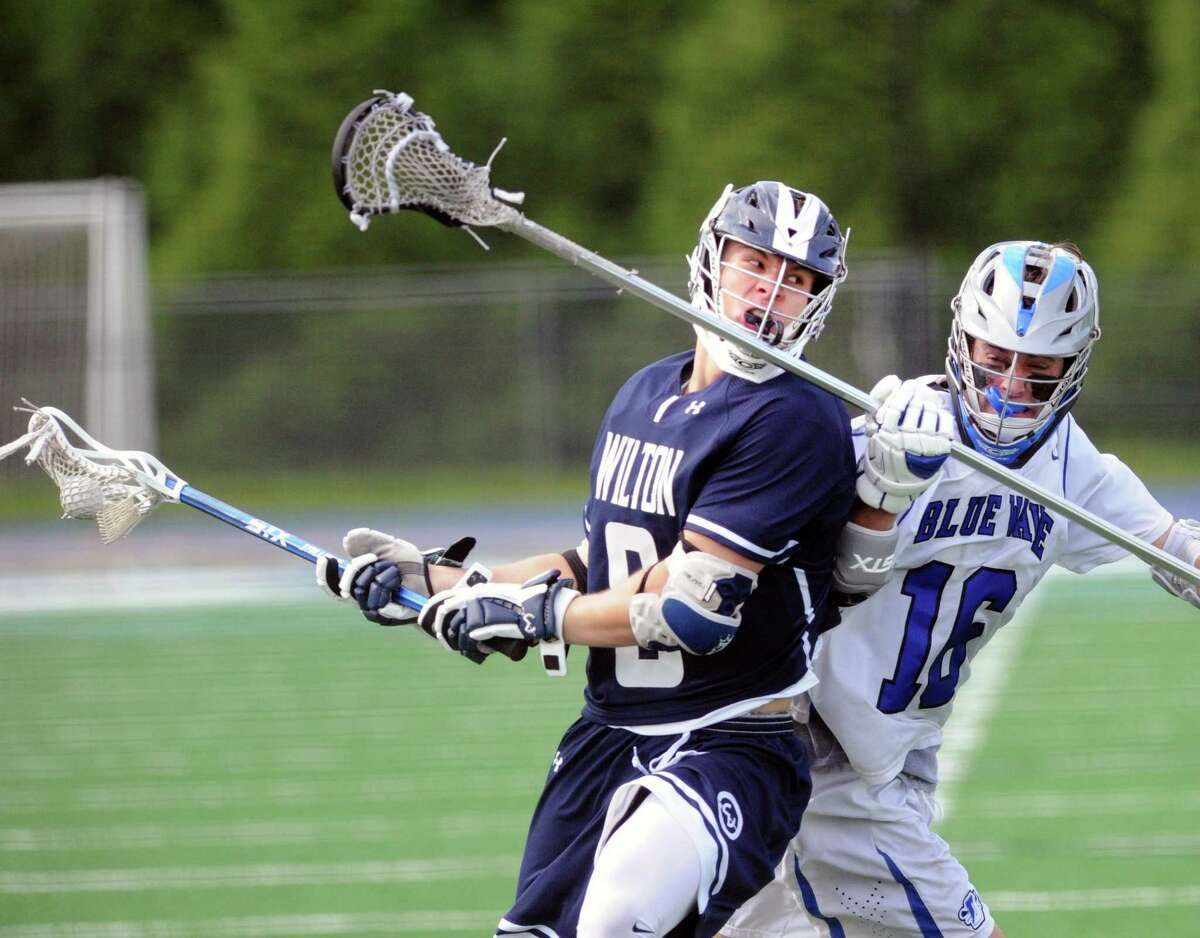 Charlie Olsen of Darien, right, defends an attacking Andrew Luciano, left, of Wilton during the closing minutes of the class L boys high school lacrosse quarterfinal match between Dairen High School and Wilton High School at Darien, Conn., Saturday, June 2, 2018. Darien won the match 11-10 over Wilton to advance.