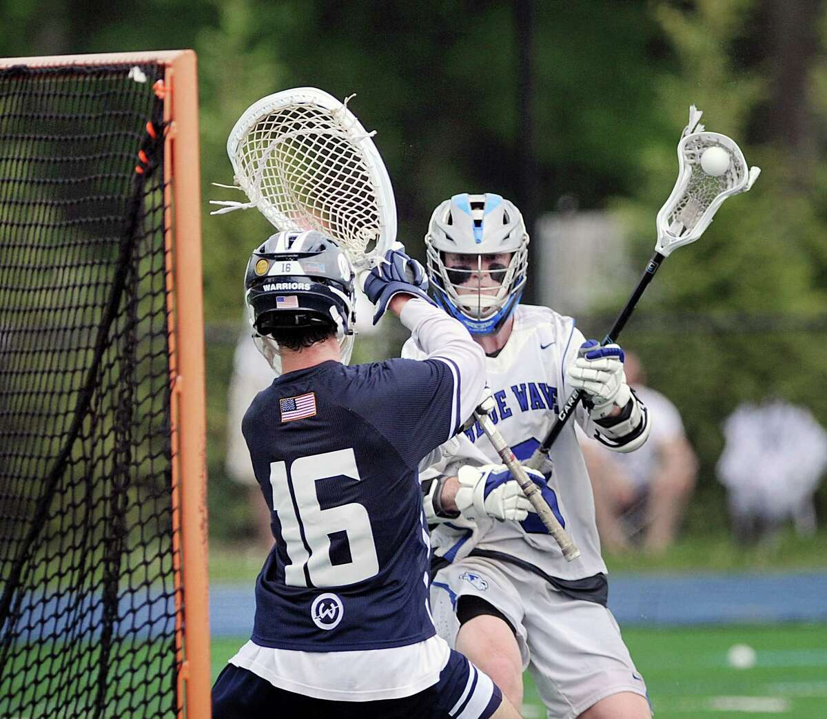 Hudson Pokorny of Darien, right, prepares to shoot as Wilton goalie Andrew Calabrese (#16) defends on a shot that he stopped during the class L boys high school lacrosse quarterfinal match between Dairen High School and Wilton High School at Darien, Conn., Saturday, June 2, 2018. Darien won the match 11-10 over Wilton to advance.