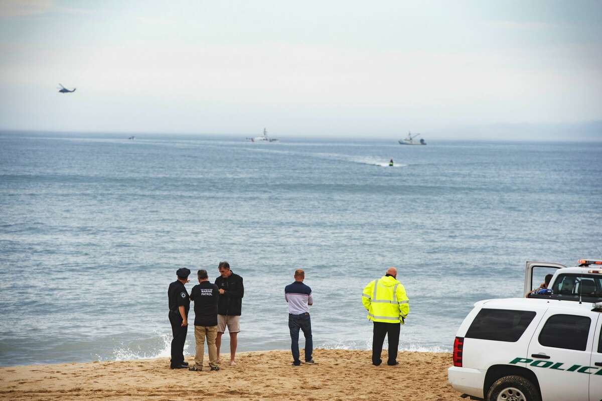 Members of the New York State park police look near the scene of a plane crash in the ocean off Indian Wells Beach in Amagansett, N.Y., Saturday, June 2, 2018. Authorities say a small plane with four people on board has crashed off the coast of New York's Long Island. The Federal Aviation Administration says the Piper PA31 aircraft went down shortly after 3 p.m. (Gordon M. Grant/Newsday via AP)
