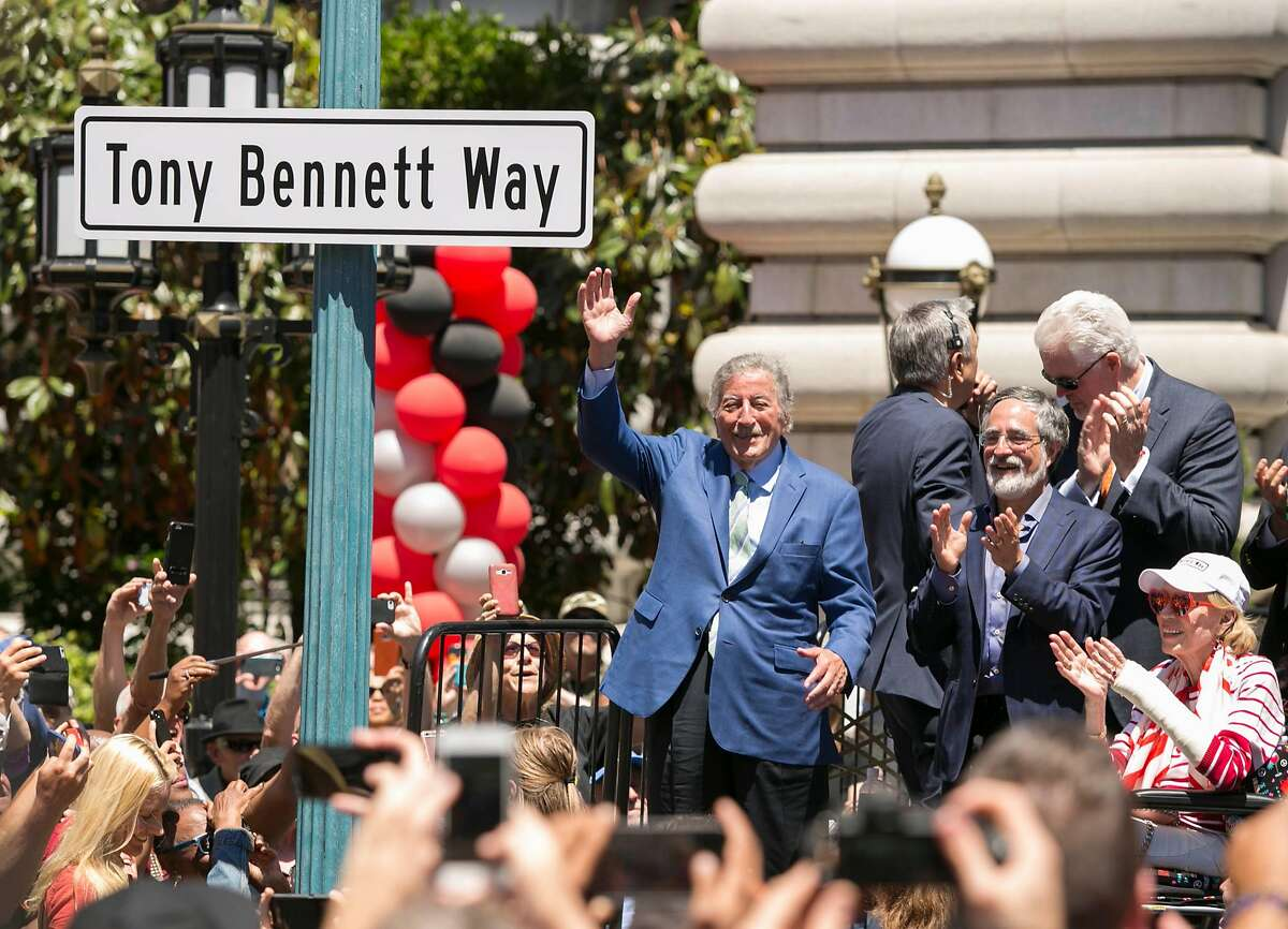 """From left, singer Tony Bennett, San Francisco Supervisor Aaron Peskin and the city's Cheif of Protocol Charlotte Schultz clap and wave to a crowd during an event where the city of San Francisco honored singer Tony Bennett by naming the section on Mason Street in front of the Fairmont Hotel between California and Sacramento """"Tony Bennett Way"""" Saturday June 2, 2018 on Nob Hill in San Francisco."""