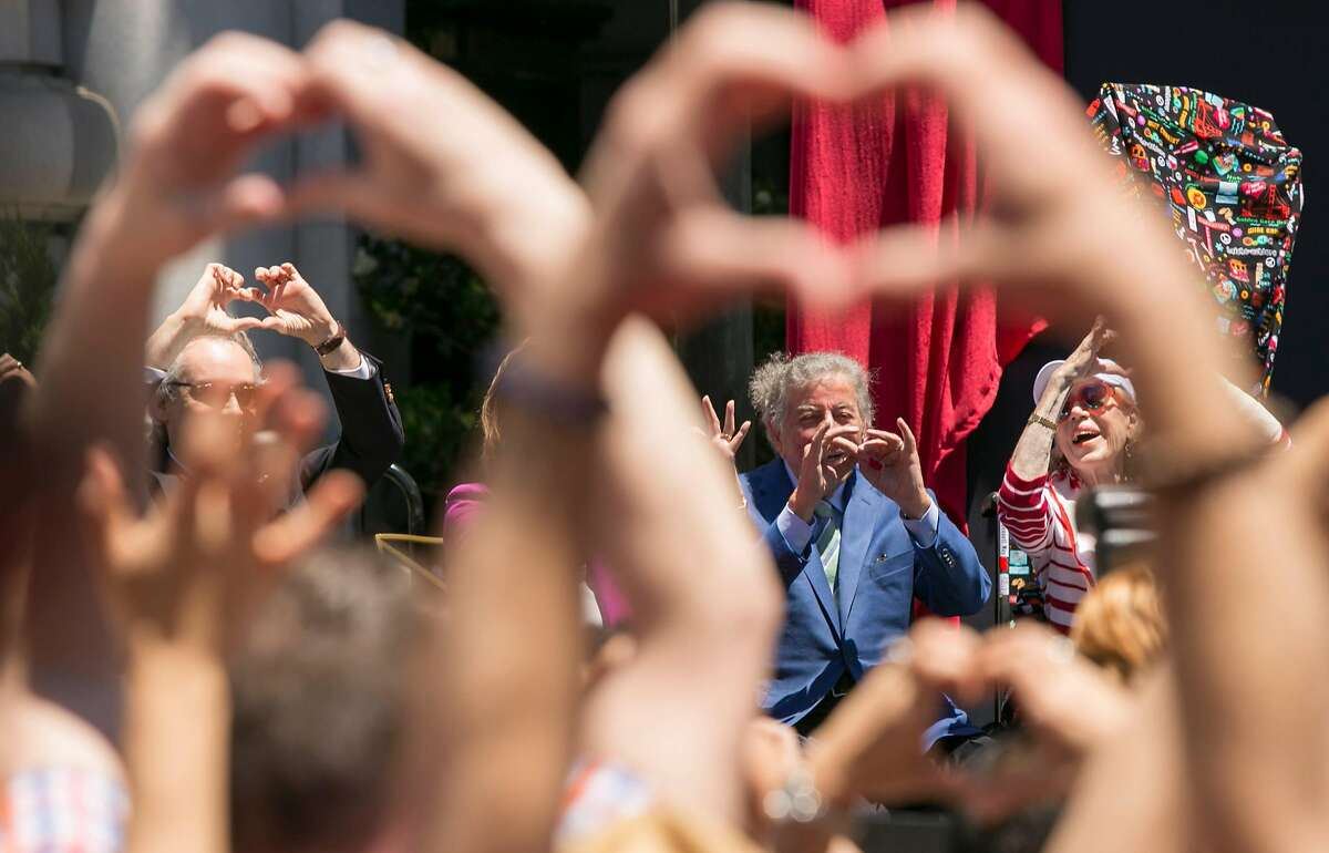 """A crowd makes heart shapes with their hands along while watching the city of San Francisco honor singer Tony Bennett by naming the section on Mason Street in front of the Fairmont Hotel between California and Sacramento """"Tony Bennett Way"""" Saturday June 2, 2018 on Nob Hill in San Francisco."""
