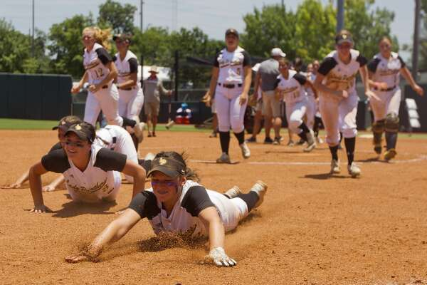 Liberty players slide on the field in celebration after defeating Vernon to Liberty 3-1 in the Class 4A state championship game during the UIL State Softball Championships at Red & Charline McCombs Field on Saturday, June 2, 2018, in Austin.