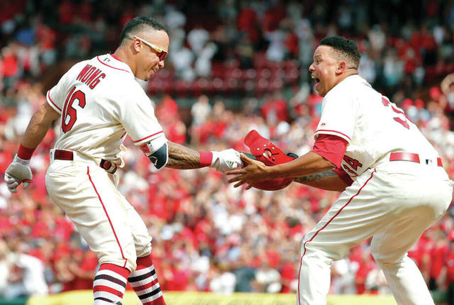 The Cardinals' Kolten Wong (left) hands his helmet to teammate Yairo Munoz while rounding the bases after hitting a walk-off home run in the ninth inning to beat the Pittsburgh Pirates on Saturday at Busch Stadium. Photo:       Associated Press