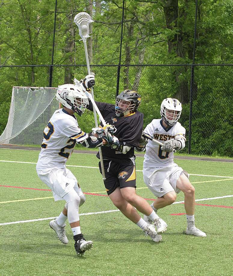 Kevin Hughes, center, of Daniel Hand is sandwiched between Weston's Jake Buffardi, left, and Peter Friedrichsen during second half action from Saturday's Class M boys lacrosse quarterfinal in Weston. Photo: John Nash/Hearst Connecticut Media