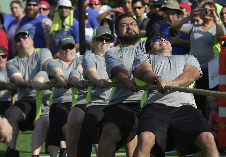 Members of the Zachry Group exert effort into the tug-of-war competition as San Antonio Sports hosts the annual Corporate Cup Challenge at the University of the Incarnate Word on Saturday, June 2, 2018. The event typically draws thousands of participants from nearly 100 area companies to compete in a series of contests, including frisbee, tug of war, basketball, relay races and more. The day-long friendly competition encouraged employee camaraderie, wellness, and athletic skill. San Antonio Sports named Corporate Cup champions in four divisions based on a company's number of employees. Winners will be based on point totals. Points were also earned prior to the event by donations to the San Antonio Food Bank, South Texas Blood & Tissue Center, Haven for Hope, Boys & Girls Club and San Antonio Sports. The overall event benefits San Antonio Sports' kids programs. (Kin Man Hui/San Antonio Express-News) Photo: Kin Man Hui, Staff / San Antonio Express-News / ©2018 San Antonio Express-News