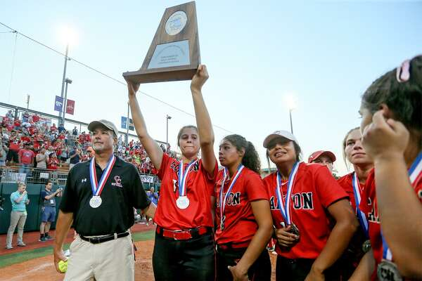 New Braunfels Canyon's Brooke Vestal hoists the runner-up trophy with coach Kevin Randle (left) and the rest of the Cougarettes at the conclusion of their UIL Class 6A state softball final with Humble Atascocita at McCombs Field in Austin on Saturday, June 2, 2018.  Atascocita beat Canyon 5-3.  MARVIN PFEIFFER/mpfeiffer@express-news.net