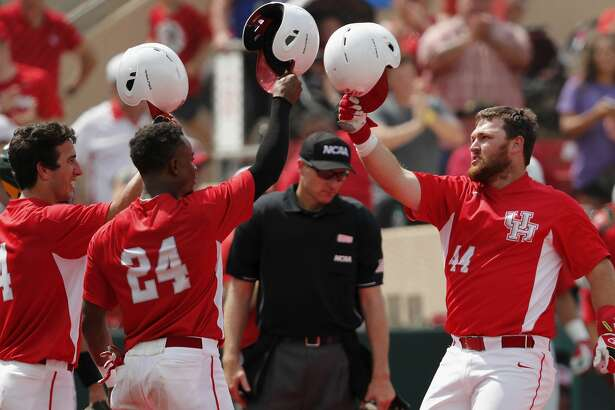 Houston Cougars first baseman Joe Davis (44) is greeted at home plate by infielder Cooper Coldiron (4) and infielder Corey Julks (24) after a sixth inning home run during the 2017 NCAA Houston Regional baseball game between the Houston Cougars and the Baylor Bears at Schroeder Park on Saturday, June 3, 2017, in Houston, TX.
