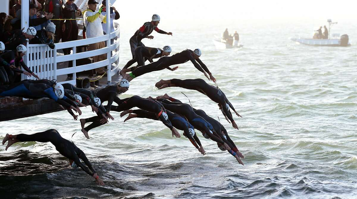 Elite competitors dive off the San Francisco Belle to begin the swimming portion of Escape From Alcatraz Triathlon hosted in San Francisco Sunday June 3, 2018.