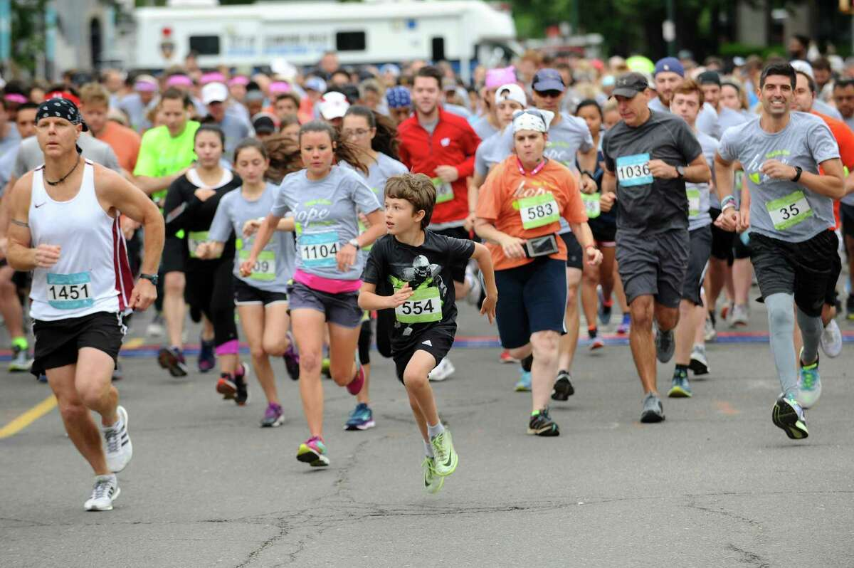 Runner Owen Fedeli (554) leads the pack as the 23rd annual Hope in Motion Walk & Run, hosted by Stamford Health's Bennett Cancer Center, kicks off at Columbus Park on Sunday.