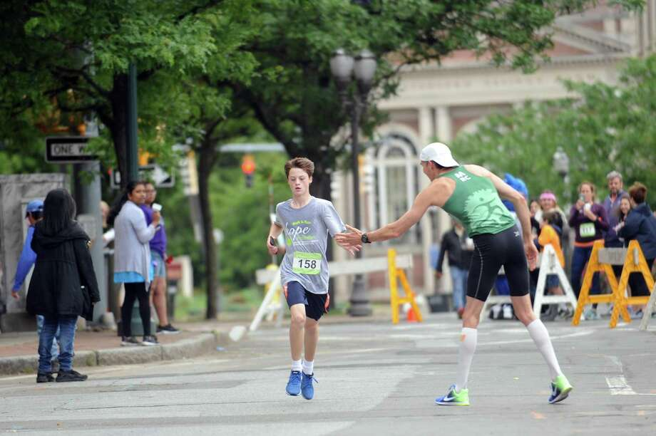 5K winner David Guzik of Fairfield, right, high-fives 15-year-old runner Tucker Healy as he reaches the final stretch of the 23rd annual Hope in Motion Walk & Run, hosted by Stamford Health's Bennett Cancer Center, at Columbus Park in downtown Stamford, Conn. on Sunday, June 3, 2018. Photo: Michael Cummo / Hearst Connecticut Media / Stamford Advocate