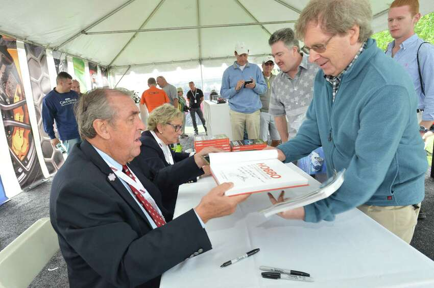Race car driver and automotive expert David Hobbs signs a copy of his new book 'Hobo' his knickname, for Redding's Tom O'Keefe during the Greenwich Concours d'Elegance at Roger Sherman Baldwin Park in Greenwich Conn. on Sunday june 3, 2018