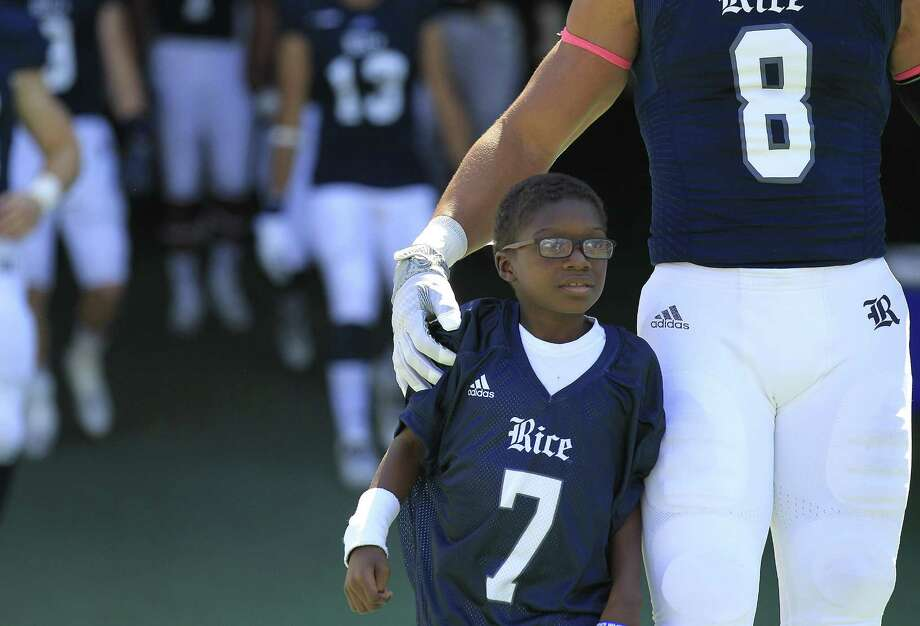 "In this 2015 file photo, Fre'derick ""Ziggy"" Stovall-Redd, 7, honorary member of the Rice University football team gets ready to take to the field with the team while defensive end Derek Brown (8) puts his arm around him. Photos of Rice University football game against Western Kentucky University at Rice Stadium on Saturday, Oct. 3, 2015, in Houston. ( Elizabeth Conley / Houston Chronicle ) Photo: Elizabeth Conley, Staff / Houston Chronicle / © 2015 Houston Chronicle"
