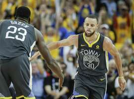 Golden State Warriors' Stephen Curry reaches for Draymond Green's hand in the fourth quarter after hitting a three-pointer during game 2 of The NBA Finals between the Golden State Warriors and the Cleveland Cavaliers at Oracle Arena on Sunday, June 3, 2018 in Oakland, Calif.