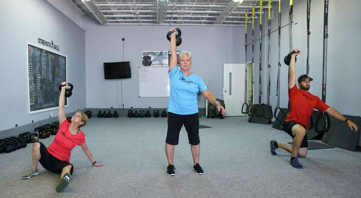 """Iron Strength Kettlebell Gym Owner and Instructor Angie Jameson, center, and instructors Tara Duncan and Eric Grimsley demonstrate different steps of a """"Turkish get-up"""" with a kettlebell for exercise on Thursday, May 31, 2018, in Sugar Land. The average Houston apartment is about 800 square feet. So how are you supposed to work out in such a small space? Fitness experts and a home organizer offer some tips to help you hack your apartment."""